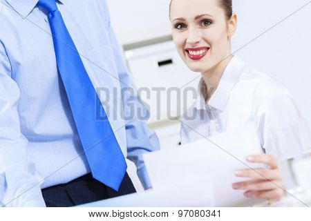 Businessman and businesswoman in office sitting at table and having conversation