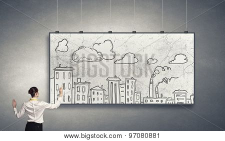 Rear view of businesswoman drawing business plan on white banner