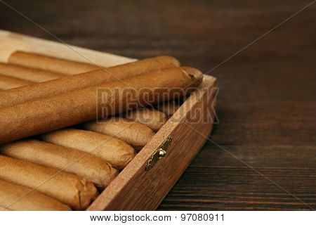 Cigars in humidor on wooden table, closeup