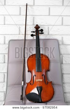 Violin on chair, on bricks wall background