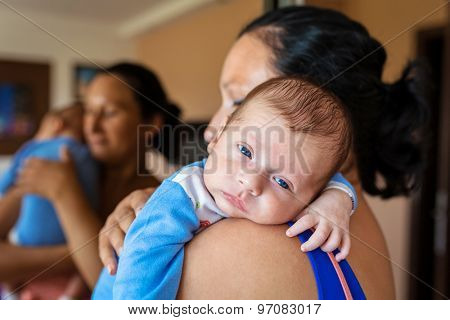 Mother cuddling her baby boy in arms
