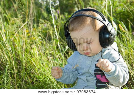 A Little Boy Sits On A Meadow With Headphones