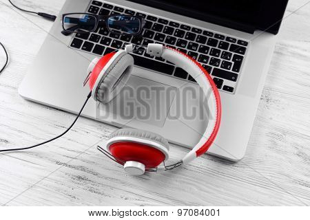 Headphones with laptop on table close up