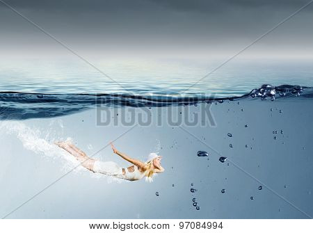 Young pretty girl in hat and dress swimming under water