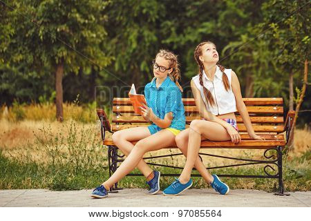 Best Friends Are Reading Diary Sitting On The Bench.