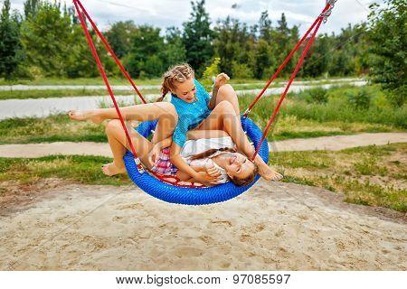 Best Girlfriends Having Fun Ride On A Swing.