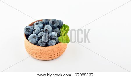 Blueberries And Mint Leaves In Wooden Bowl Isolated On White