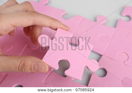 Female hand placing last piece of puzzle, closeup