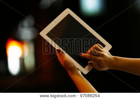 Female hands with tablet on blurred night lights background