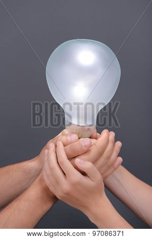 Light bulb in hands on grey background
