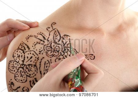 Process of applying Mehendi on female shoulder, on white background