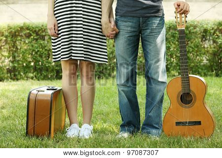 Young couple with vintage suitcase and guitar outdoors