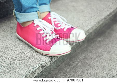 Female feet in pink gumshoes on stone stairs