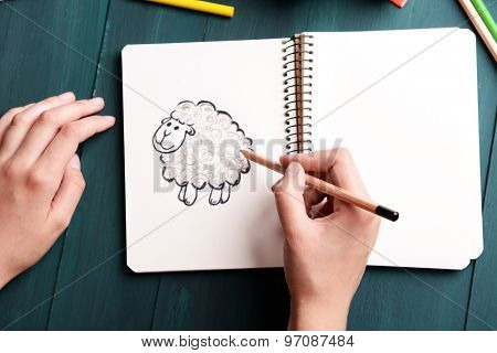 Female hands drawing sheep in notebook on wooden table background