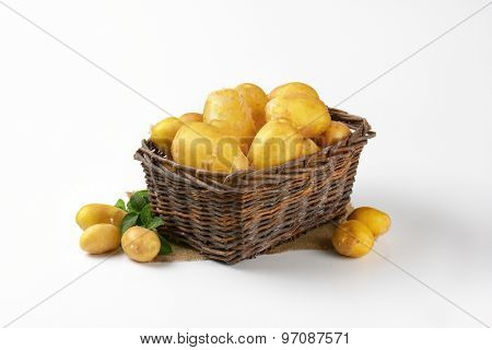 fresh baby potatoes in brown wicker basket on white background