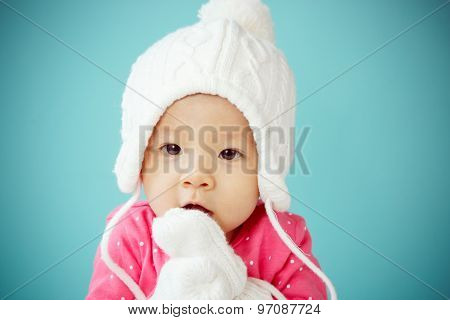 Little Baby In Knit Winter Clothing Closing Face With Knitted Beanie