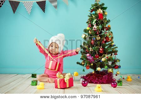 Little Baby Open The Gift Box With Decorating Christmas Tree On Green Background