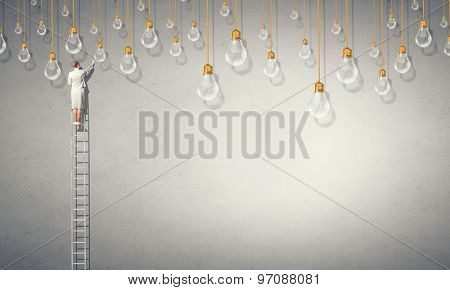 Back view of businesswoman standing on ladder and reaching light bulb
