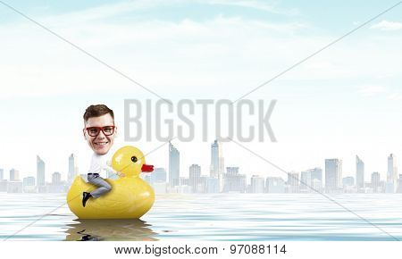 Silly young businessman in work break riding on plastic duck