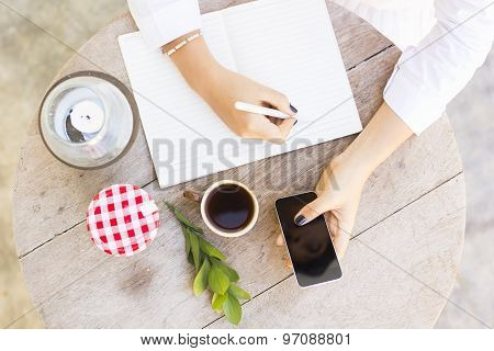 Girl Writes In Notebook With Cell Phone And Cup Of Coffee, Top View