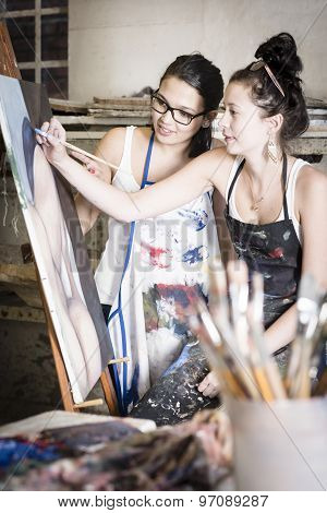 Two Young Artists Working Together On A Painting