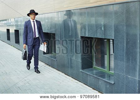 Elegant businessman in suit and hat walking along modern building wall