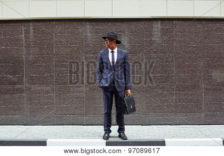 Handsome businessman in suit, hat and eyeglasses standing by wall of modern building