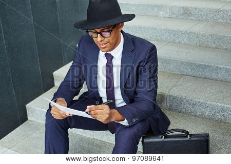 Elegant businessman in suit, hat and eyeglasses making notes while sitting on stairs