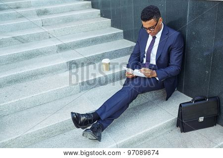Confident businessman making notes while working outside