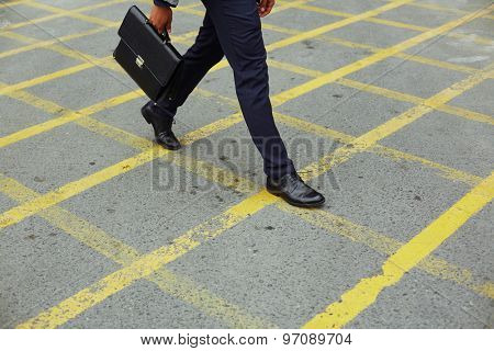Legs of businessman with briefcase going to work