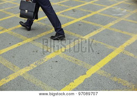 Modern businessman in formalwear walking down trottoire