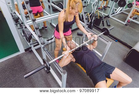 Woman coach helping to man in bench press training