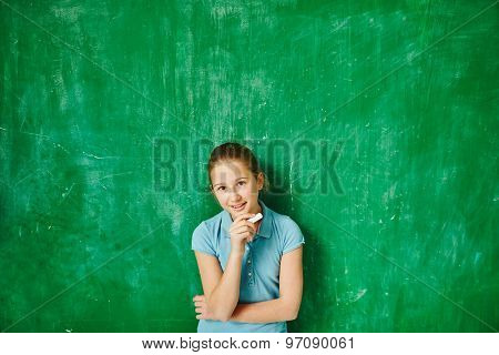 Clever pupil with chalk looking at camera by blackboard