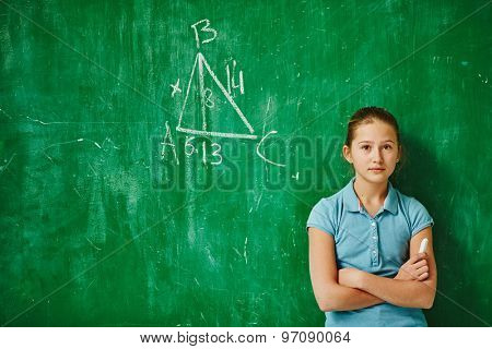 Cute schoolgirl looking at camera while standing by blackboard with geometric task on it