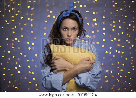 Young female in pyjamas holding pillow and looking at camera on sparkling background