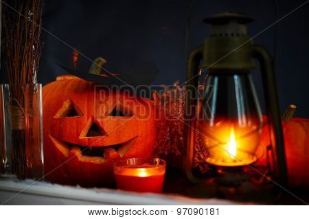 Carved Halloween pumpkin with burning lantern and candle near by