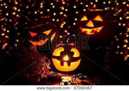 Jack-o-lanterns and Halloween spiders on sparkling background