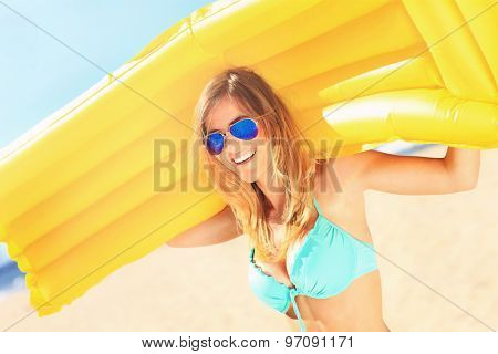 A picture of a beautiful woman with mattress on the beach