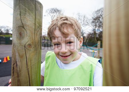 Boy On Climbing Frame In School Physical Education Class