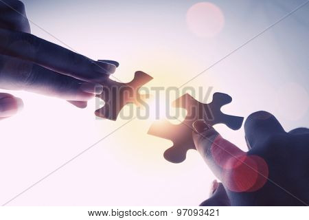 Close up of hands connecting puzzle element and making jigsaw complete
