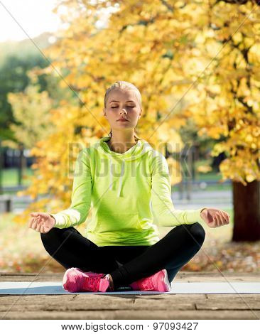 sport and lifestyle concept - woman doing yoga outdoors