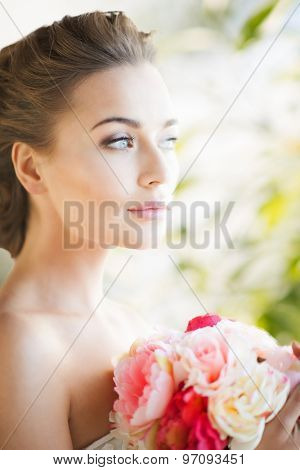 lovely bride with bouquet of flowers indoors
