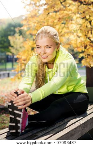 fitness and lifestyle concept - woman doing sports in autumn park