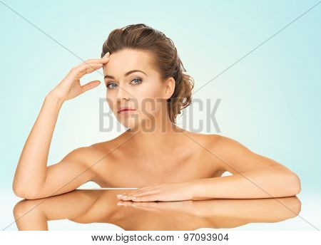 close up of beautiful woman lying on the mirror