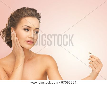 beautiful woman looking at wedding ring and thinking