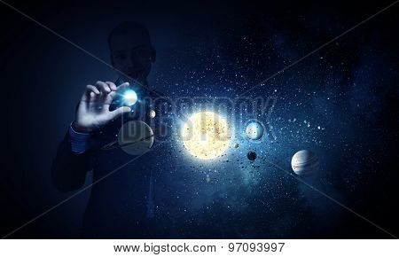 Young businessman catching planet of sun system