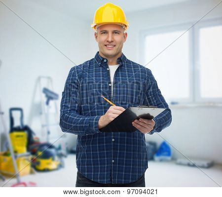 repair, construction, building, people and maintenance concept - smiling male builder or manual worker in helmet with clipboard taking notes over room with work equipment background