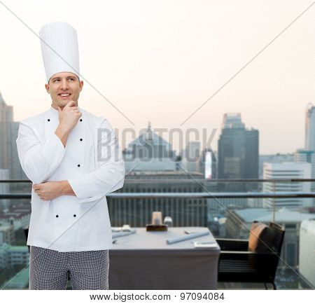 cooking, profession, inspiration and people concept - happy male chef cook thinking over city restaurant lounge background