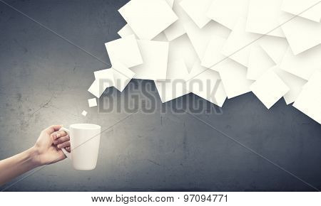 Hand holding coffee cup with flying out papers