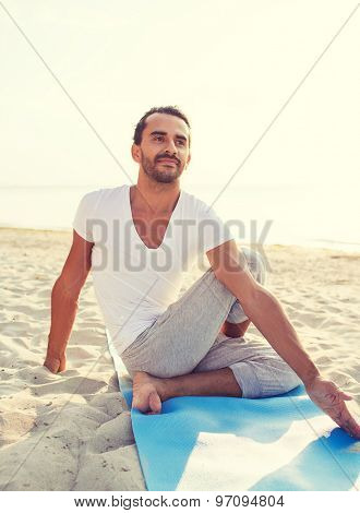 fitness, sport, people and lifestyle concept - man doing yoga exercises sitting on mat outdoors